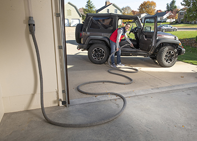 Vroom Retract Vac cleans Jeep in driveway
